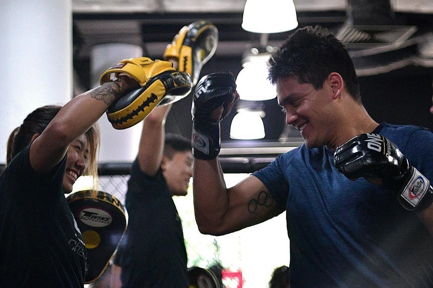 Olympic champion Joseph Schooling tries his hand at mixed martial arts during a training session with One Championship atomweight titleholder Angela Lee last November. He will be in her entourage in May.