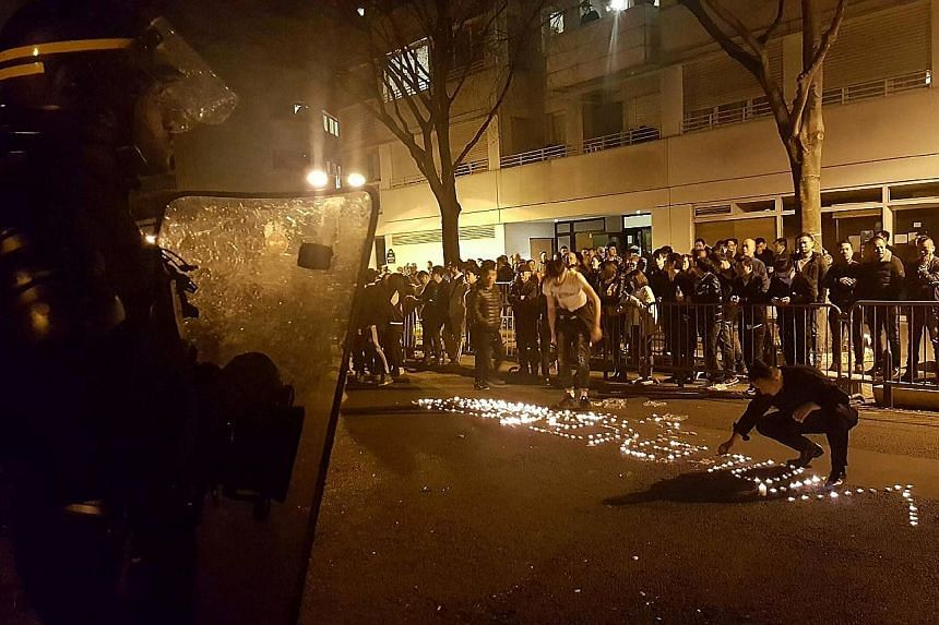 "Protesters spelling the word ""violence"" with candles on a street in front of a line of riot policemen in Paris late on Monday, during clashes that took place after police killed a Chinese father of four."