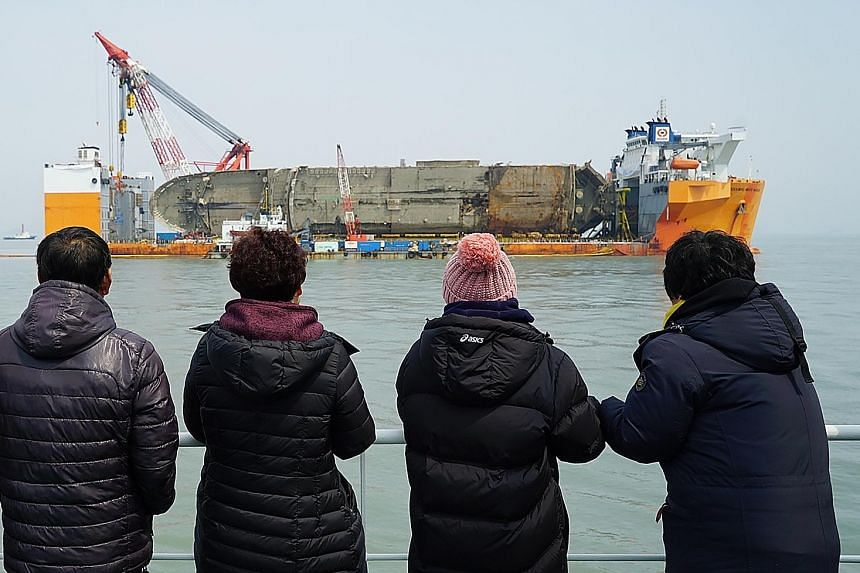 Relatives of the missing victims from the Sewol ferry disaster looking at the damaged vessel during a memorial service on a ship off the coast of the southern South Korean island of Jindo yesterday. The ferry sank nearly three years ago, with nine vi