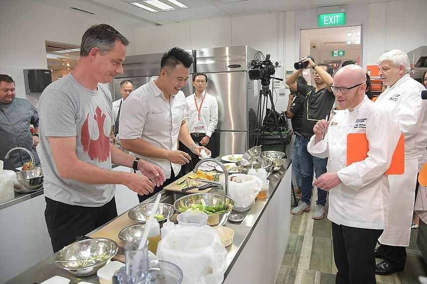 Michael di Placido (far left) from Stellar Restaurant and Nixon Low from Jiakpalang Eating House take part in a 30-minute cooking challenge as Gary Maclean (second from right) and Mr Willie McCurrach look on, at the opening of the MDIS baking and cul
