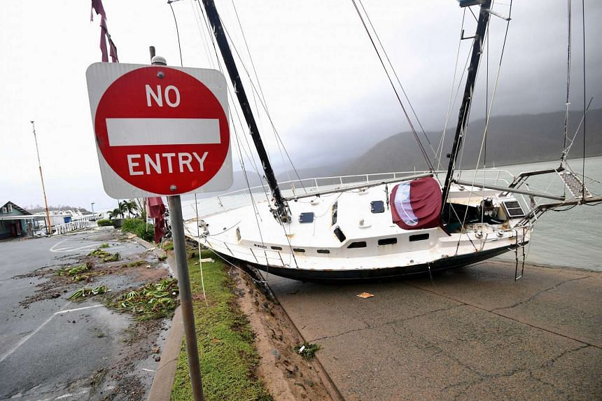 A boat is smashed against the bank at Shute Harbour, Airlie Beach, on March 29, 2017.
