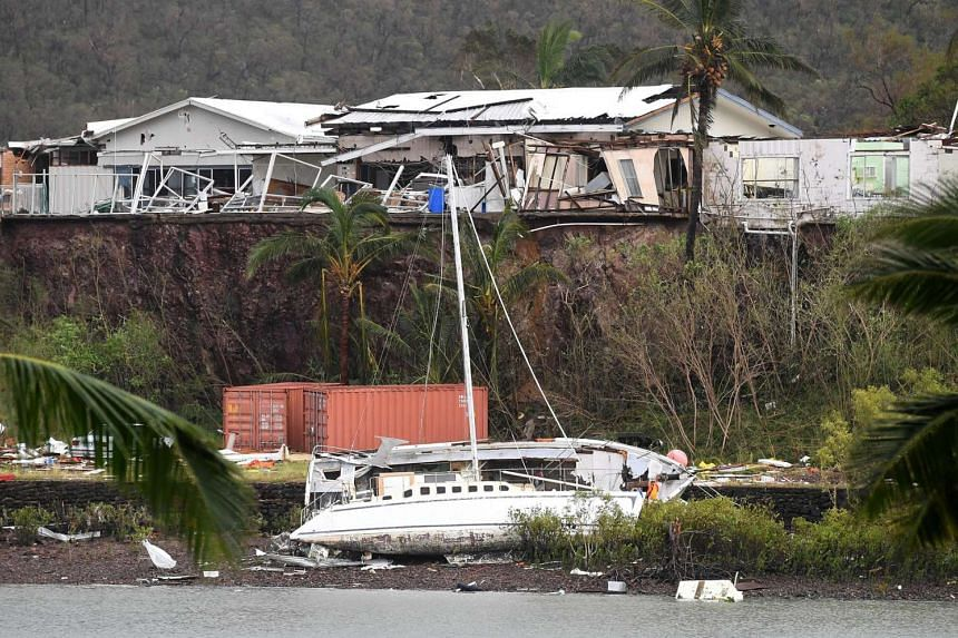 A damaged building is seen behind a boat that was pushed onto a bank due to Cyclone Debbie in the township of Airlie Beach, located south of the northern Australian city of Townsville.