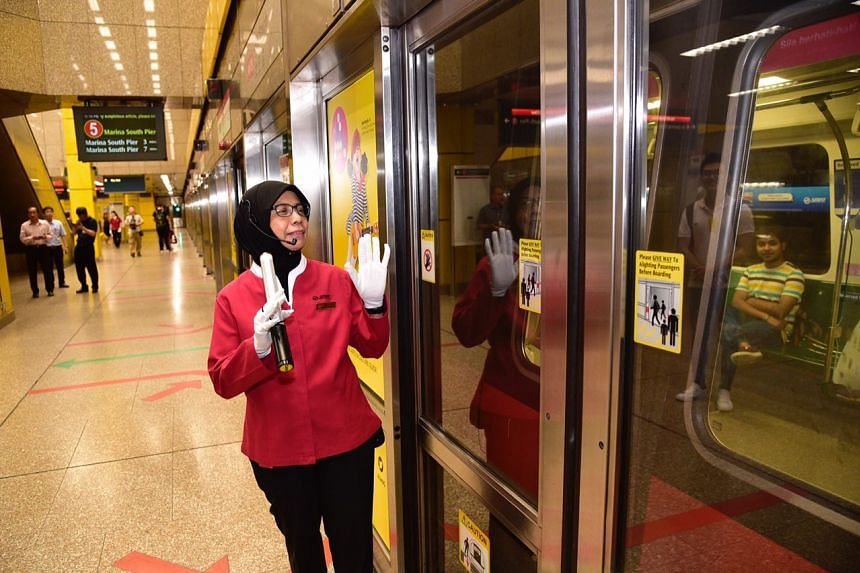 SMRT service staff assisting commuters during the 10-minute stoppage.