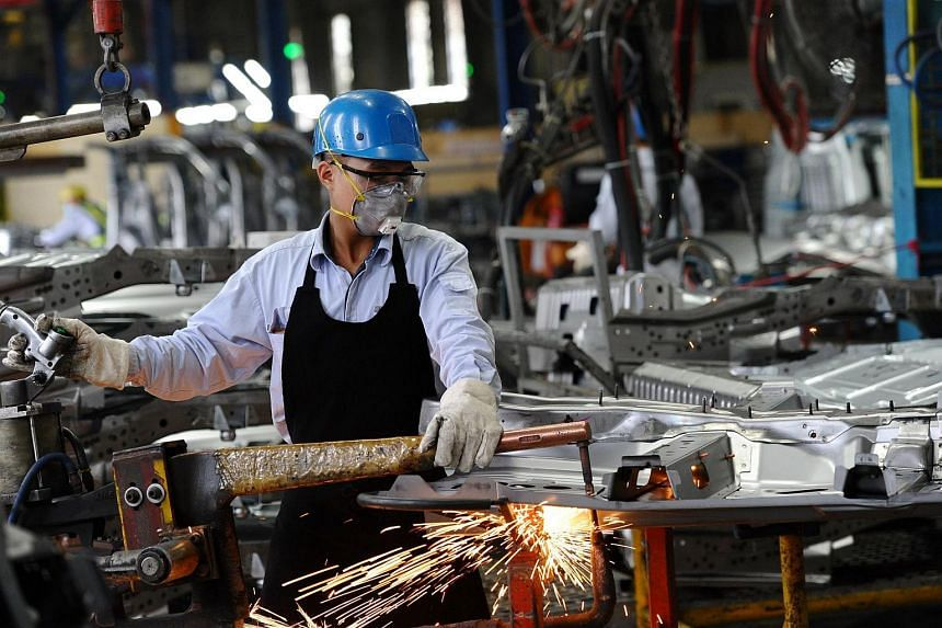 A Vietnamese worker welding in the body shop at the Ford automotive plant in the northern province of Hai Duong, on Jan 11, 2017.