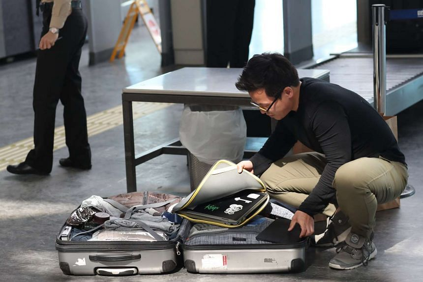 Passengers open their luggage and show their electronic equipment at a security point at the Ataturk Airport, in Istanbul, Turkey.