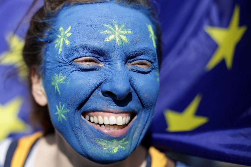 A woman with her face painted in the colours of the EU flag takes part in an anti-Brexit protest in London, March 25, 2017.