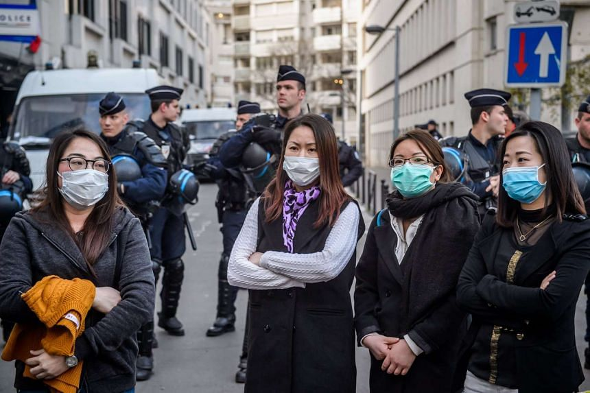 Members of the French Chinese community gather outside a police station to protest against police violence in Paris, March 28, 2017.