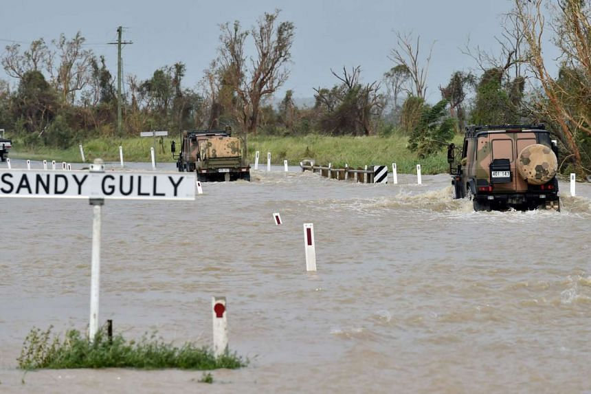 Army vehicles driving through floodwaters near the Queensland town of Bowen on March 29, 2017, after the area was hit by Cyclone Debbie.