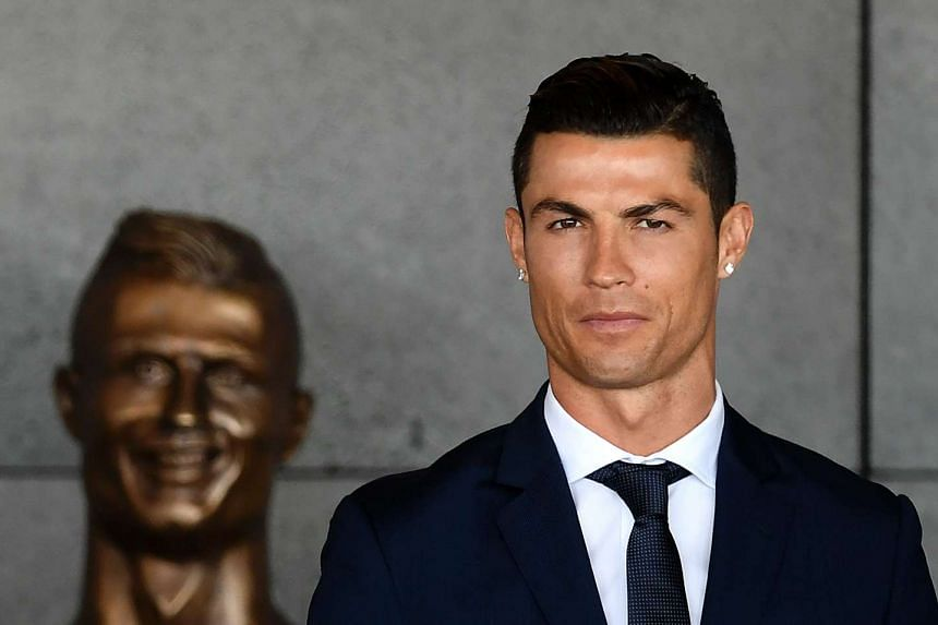 Soccer star Cristiano Ronaldo standing next to the bust created by self-taught sculptor Emanuel Santos.