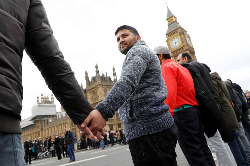People hold hands on Westminster Bridge during the vigil.