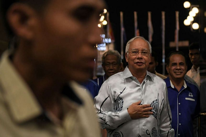PM Najib (centre) arrives for an UMNO supreme council meeting in Kuala Lumpur on March 29, 2017.