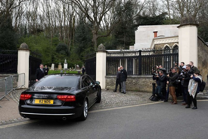 A car drives past members of the media outside Highgate Cemetery in London, March 29, 2017.