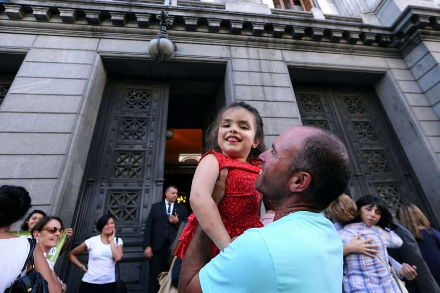 Josefina Vilumbrale, who suffers from refractory partial epilepsy and has been treating her illness with cannabis, is held by her father, Fernando Vilumbrale, as they wait outside the Congress for the Senate to pass a law to legalise the medical use