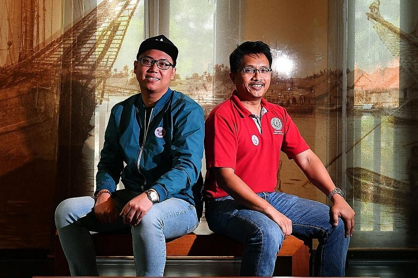 Mr Abdul Wafi Abdul Raib (far left) and Mr Sarafian Salleh are co-founders of the Bugis Temasek online community. Behind them at the Malay Heritage Centre is an image of the distinctive Bugis trading vessel, the pinisi.