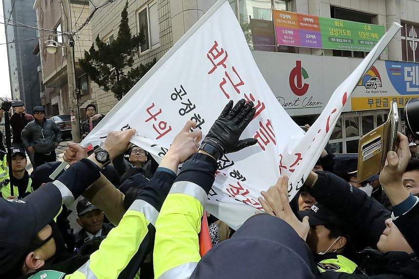 A man demanding Ms Park's arrest is restrained during a protest near her home in Seoul yesterday. A court will rule tomorrow on a warrant seeking her arrest over alleged corruption.
