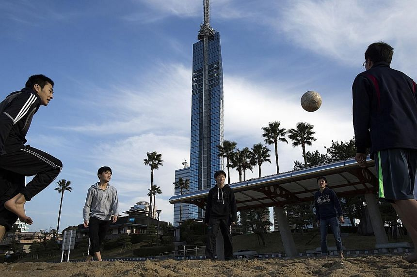 A soccer game at a seaside park, with Fukuoka Tower in the background. Fukuoka is the fastest-growing major city in Japan outside of Tokyo. Mr Watabe moved to Fukuoka in 2013 to develop smartphone apps and software that helps anglers find fish and sh