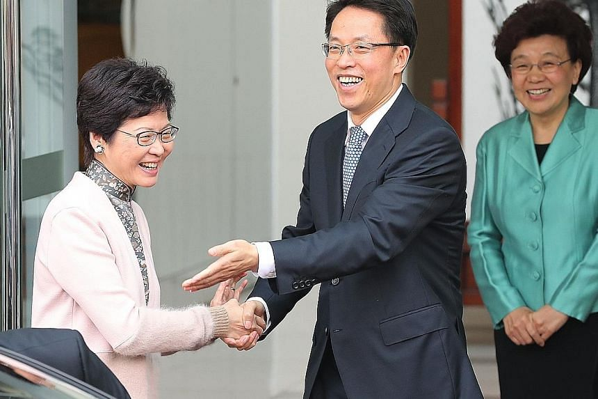 """Hong Kong Chief Executive-elect Carrie Lam greeting the director of Beijing's liaison office in Hong Kong, Mr Zhang Xiaoming, during her visit yesterday. Beside them is the office's deputy director Yin Xiaojing. Mrs Lam said Hong Kong has """"lost a few"""