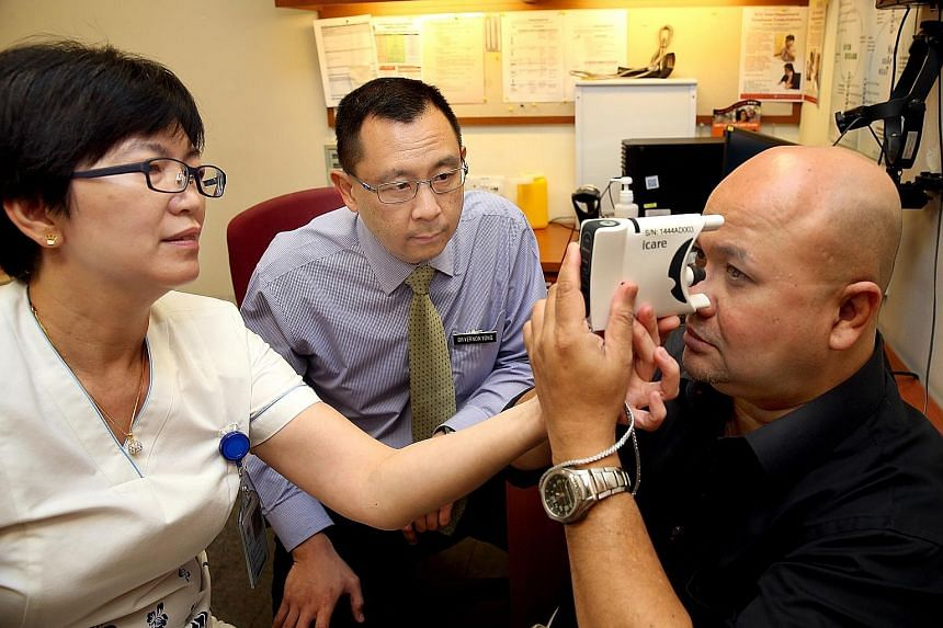Assistant nurse clinician Soo Hoo Wai Cheong and Dr Vernon Yong helping patient Shaun Nathan use a handheld device to measure his eye pressure. With the device, which can be used at home, glaucoma patients do not have to make multiple trips to the ho