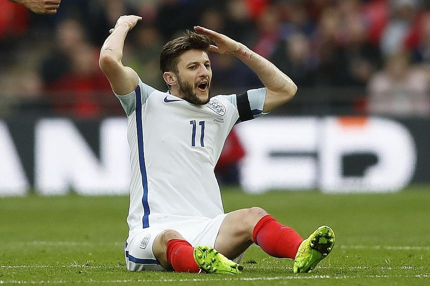 England's Adam Lallana reacts after being fouled during England's World Cup qualifier against Lithuania.