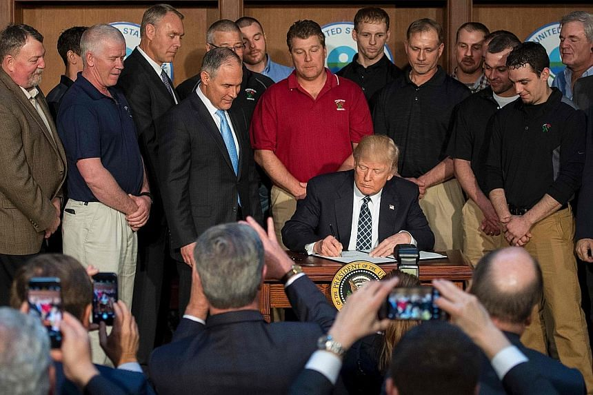 US President Donald Trump, surrounded by miners, signing the Energy Independence Executive Order at Environmental Protection Agency headquarters in Washington. The move has prompted international concern over the United States' commitment to fighting