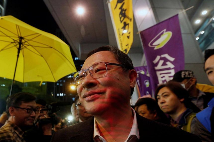 Benny Tai, a founder of the Occupy Central movement, surrounded by supporters as he is walking into the police headquarters in Hong Kong, on March 27, 2017.