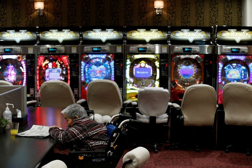 An elderly man sits in front of pachinko machines at an adult daycare centre named Day Service Las Vegas in Tokyo.
