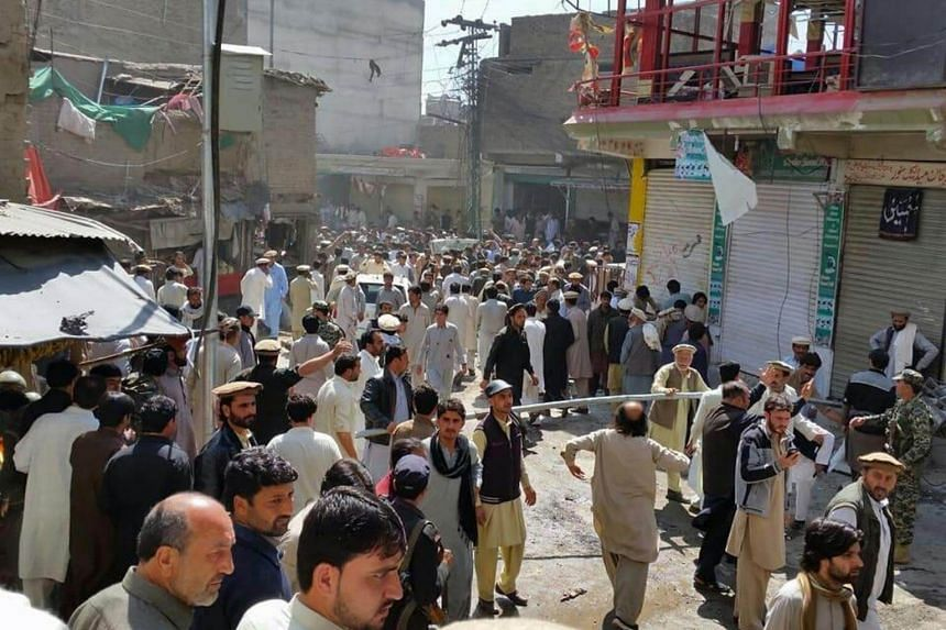 People survey the site of a suicide bomb blast near a mosque in the Noor market of Parachinar.