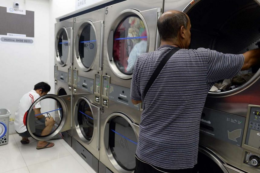 Customers putting laundry into coin-operated washing machines at Ocean Wash laundromats in Circuit Road.