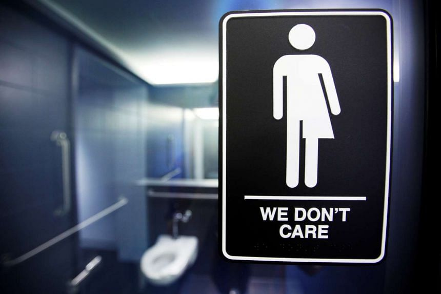 A sign protesting a recent North Carolina law restricting transgender bathroom access adorns one of the stalls at the 21C Museum Hotel in Durham, North Carolina.