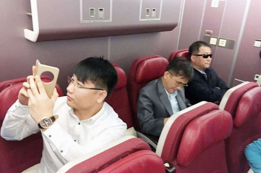 Passengers believed to be North Koreans including Kim Uk Il (left) inside an airplane for a flight to Beijing, at an airport in Kuala Lumpur, Malaysia.