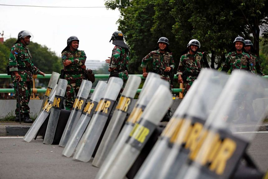 Indonesian soldiers stand guard near the presidential palace ahead of a planned protest calling for the removal of Jakarta's governor in Jakarta on March 31, 2017.