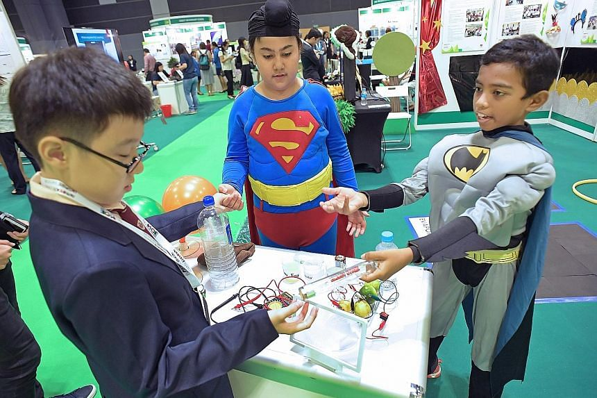Meherdeep Singh (in Superman costume) and Karthikeyan Muthukumar (in Batman costume), both Primary 5 pupils at Bukit View Primary School, demonstrating a science experiment yesterday at the Ministry of Education ExCEL Fest.