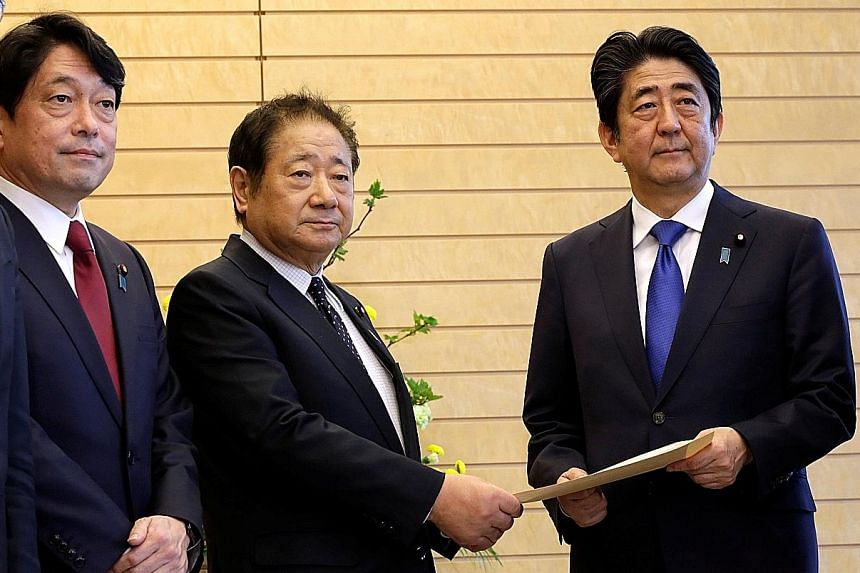 Mr Abe receiving a proposal on missile defence from Mr Hiroshi Imazu, chairman of the Research Commission on Security of Japan's ruling Liberal Democratic Party, who is accompanied by former defence minister Itsunori Onodera at the Prime Minister's O