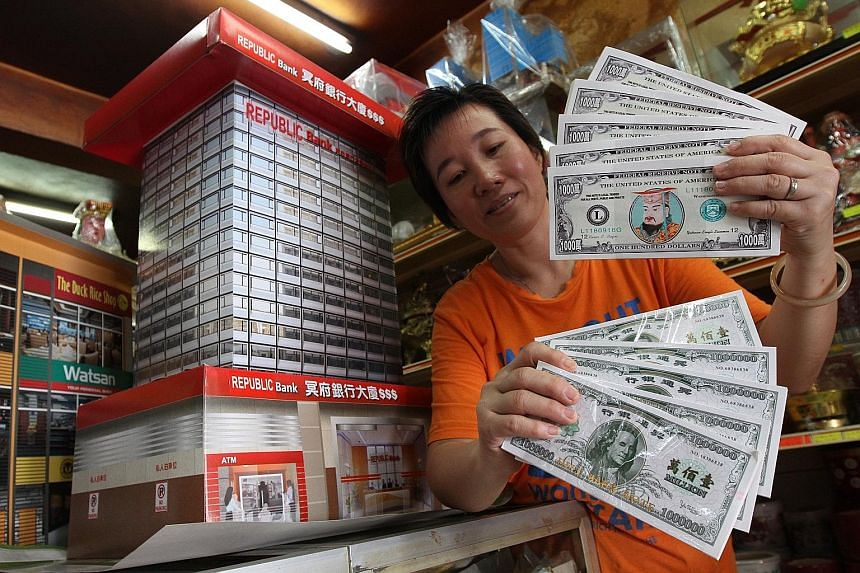 """""""Hell money"""" resembling US dollar notes, like the ones shopkeeper Ang Siew Siew sells at her shop in Penang, Malaysia, is in demand. Due to the weakening ringgit, there has been a surge in demand for fake cash - called hell money - resembling strong"""