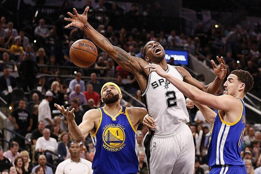 San Antonio small forward Kawhi Leonard is fouled by Golden State shooting guard Klay Thompson at AT&T Centre, as centre JaVale McGee provides cover. The visitors trailed badly but rebounded to win 110-98 and could face the Spurs again in the Western