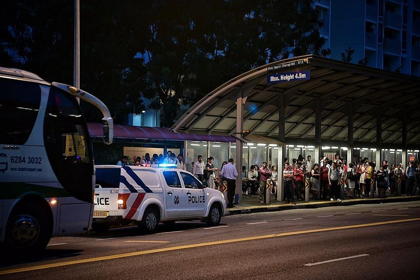 Commuters waiting for free bus services outside Tanah Merah MRT station yesterday evening as train services on the East-West Line between Pasir Ris and Paya Lebar towards Joo Koon were delayed by up to 40 minutes. A police car was stationed there to