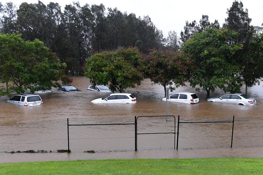 Heavy rain left large areas of Queensland, Australia, including this Gold Coast suburb of Robina, submerged in floodwaters yesterday, as Cyclone Debbie swept down the coast. The cyclone hit as a Category Four storm in the north of Australia's tropica