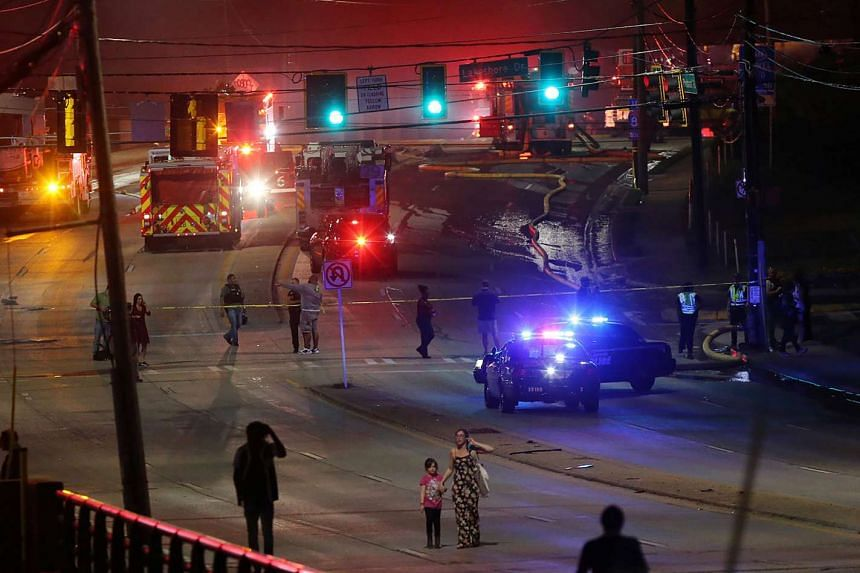 People make their way away from the bridge fire on Piedmont Road as emergency personnel work at the scene.