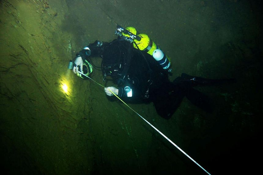 Undated handout photo of a diver searching for a new record depth at Hranice Abyss, already identified as the world's deepest underwater cave, near Hranice, Czech Republic.