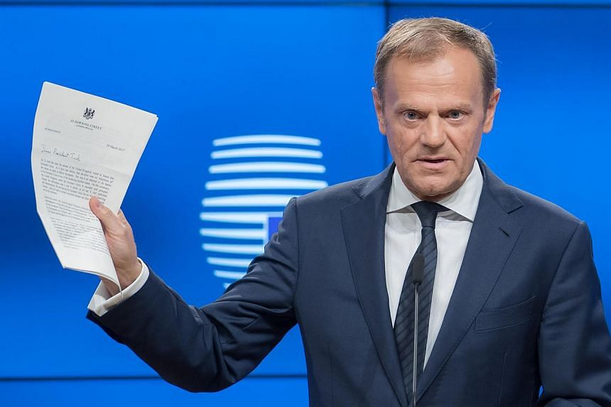 EU President Donald Tusk holds the letter invoking Article 50 of the Lisbon Treaty from the UK Prime Minister as he speaks during a news conference at the European Council in Brussels.