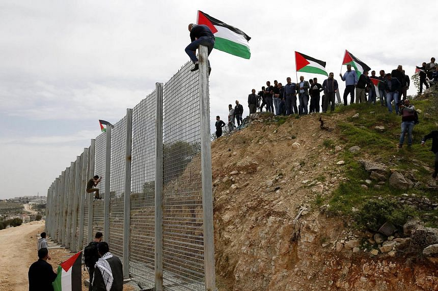 Palestinians put the Palestinian flag on the Israeli wall during a protest to mark land day in the West Bank city of Biet Jala.