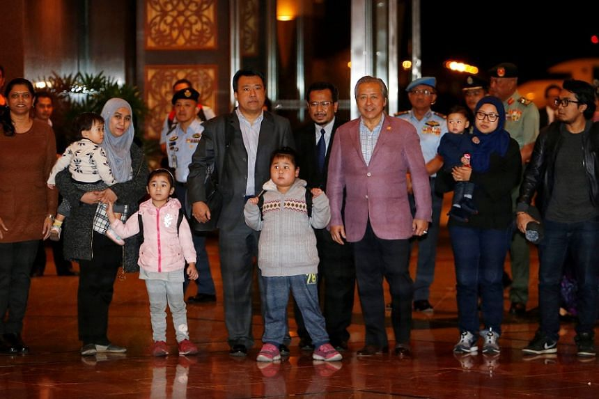 Malaysia's Foreign Minister Anifah Anan (third from right) walking with the nine Malaysian citizens who were previously stranded in Pyongyang as they return home at the Kuala Lumpur International Airport, on March 31, 2017.