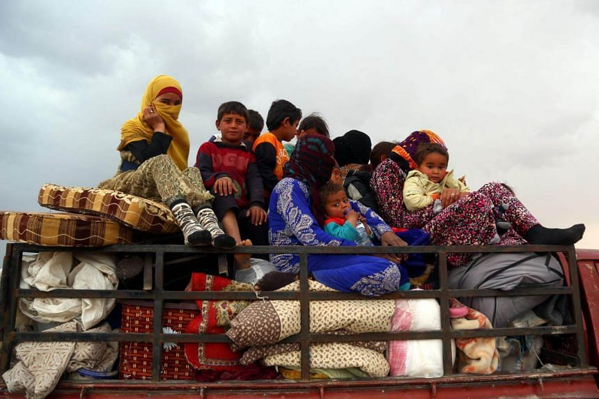 Syrian refugees arrive in the village of Suwaidiya Saghira, north of Tabqa, on March 30, 2017, after fleeing their homes.