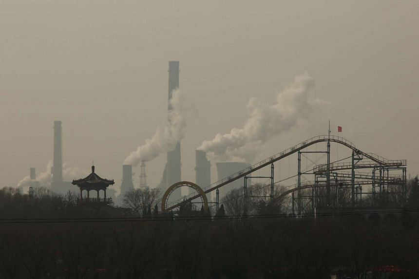 Cooling towers emit steam and chimneys billow in an industrial zone in Wu'an, Hebei province, China on Feb 23, 2017.