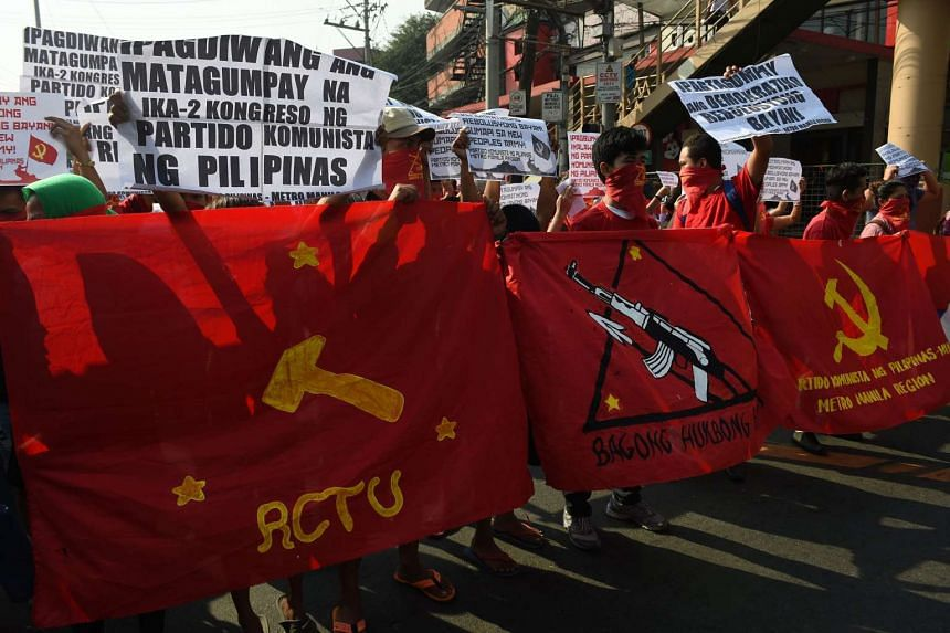 Members and supporters of the New People's Army (NPA) raise clinched fists during a protest at the peace arch near Malacanang Palace in Manila on March 31, 2017.
