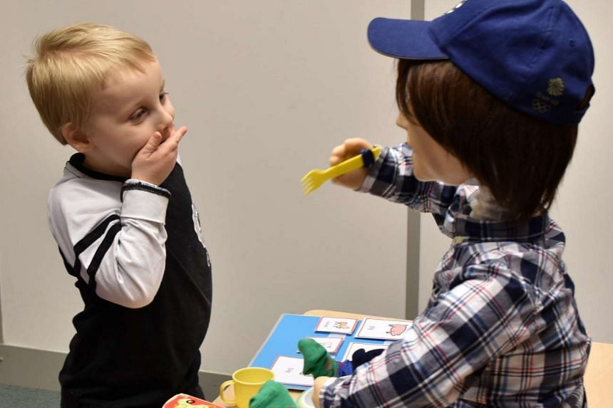 Harrison, 5, who is autistic, playing with Kaspar, a humanoid robot developed at the University of Hertfordshire to interact and help improve the lives of children with autism, in Stevenage, Britain.
