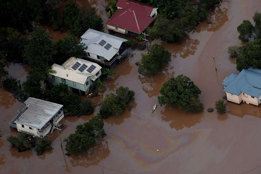 A person kayaks through floodwaters as houses remain underwater after the levee was breached in Lismore, New South Wales, on Saturday (April 1).