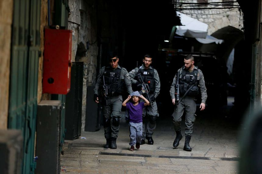 Israeli border police escort a boy who was not involved in the incident away from the scene.