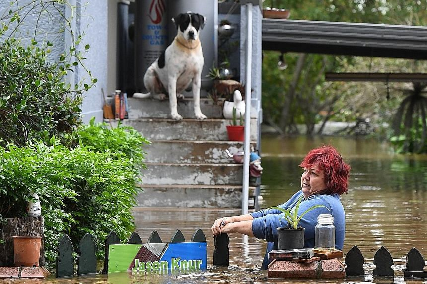 A woman attempting to gain access to her home as her dog looks on in Lismore in New South Wales as floodwaters swirl around her. The Lismore region has been declared a natural disaster zone. An aerial view (right) of houses in Lismore hit by extensiv