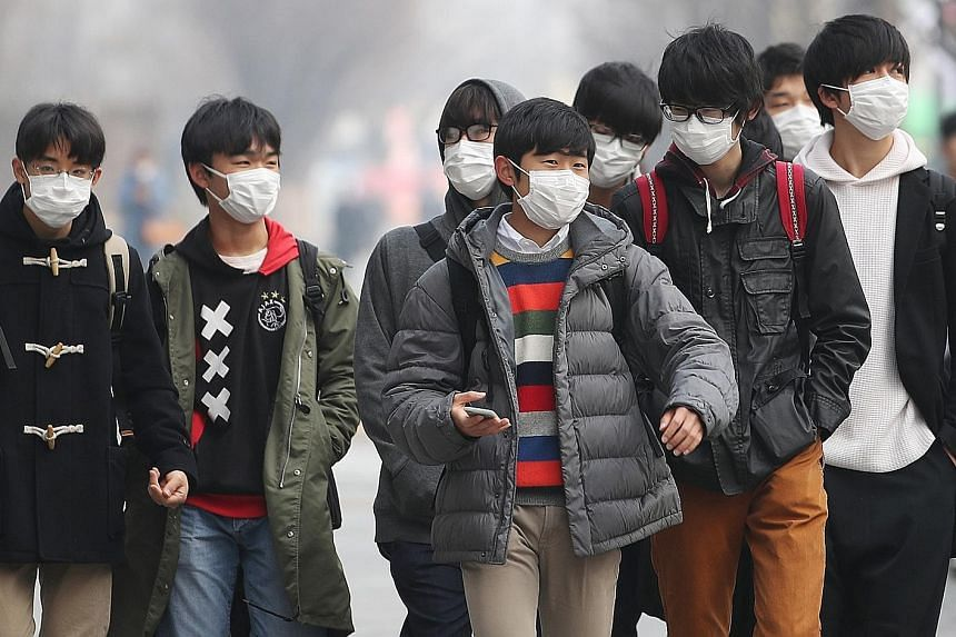 Students in Gwanghwamun Square in central Seoul on Tuesday. The government has issued multiple health warnings over ultra-fine pollutant particles, and local media has reported that sales of portable pollution monitors, face masks and air purifiers h